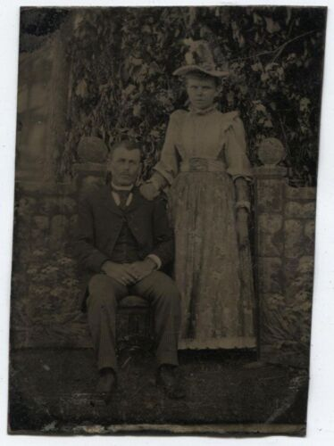 ANTIQUE TINTYPE COUPLE IN AFFECTIONATE POSE, RICHLY TEXTURED PAINTED BACKGROUND.