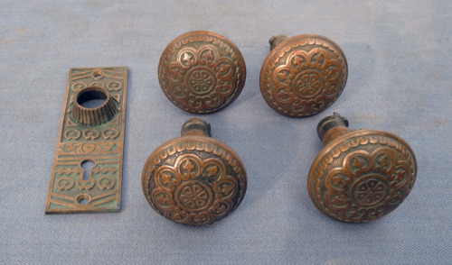 FOUR VINTAGE ORNATE BRASS KNOBS AND ONE DOOR PLATE
