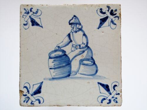A Dutch Delft tile with a market sales woman between her goods.....