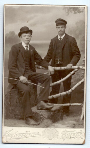 1907 two young men in suits lean on fence, Boras, Sweden; small cabinet photo