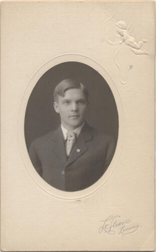 SILVER GELATIN MOUNTED TO BOARD, OVAL CUT, YOUNG MAN WITH A LAPEL PIN. MICH.