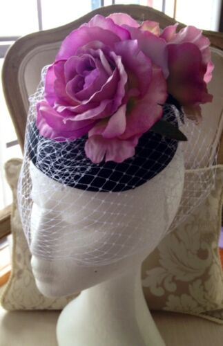 Elegant black round base fascinator with purple flowers and white netting!