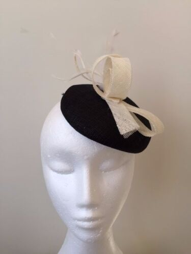 Beautiful black button base fascinator with white sinamay loops and flowers!