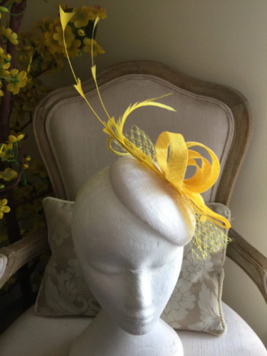 Gorgeous white coloured round fascinator yellow loops, feathers and netting.