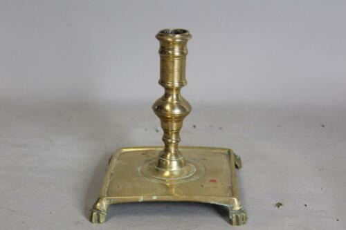 A FANTASTIC EARLY 17TH C SQUARE BASE SPANISH BRASS CANDLESTICK BRUSHED PAW FEET
