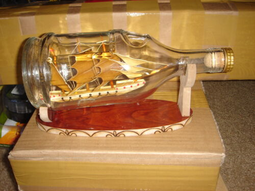 Bamboo hand made model ship in a round glass bottle
